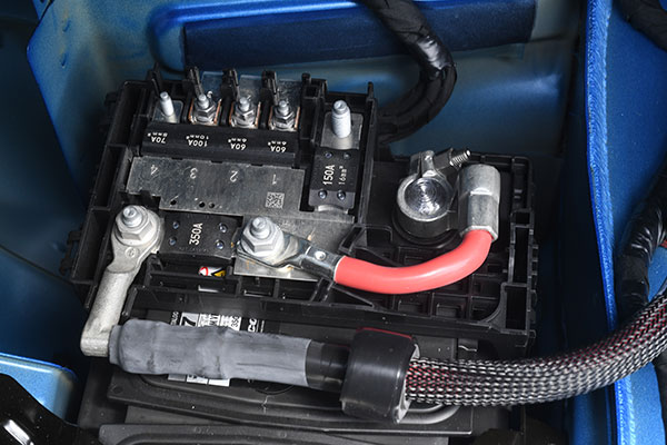 This is the Cadillac battery fuse block. To remove it, you disconnect the short cable from the battery positive post, release the two latches, then fold it back over the adjacent trunk floor. Image: Author.